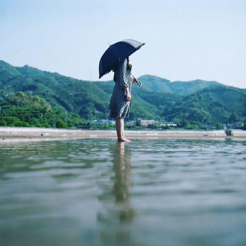 Woman Holding Umbrella On Beach Against Clear Sky