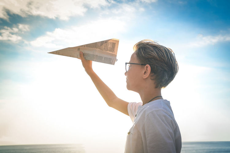 Boy holding paper airplane standing by sea against sky