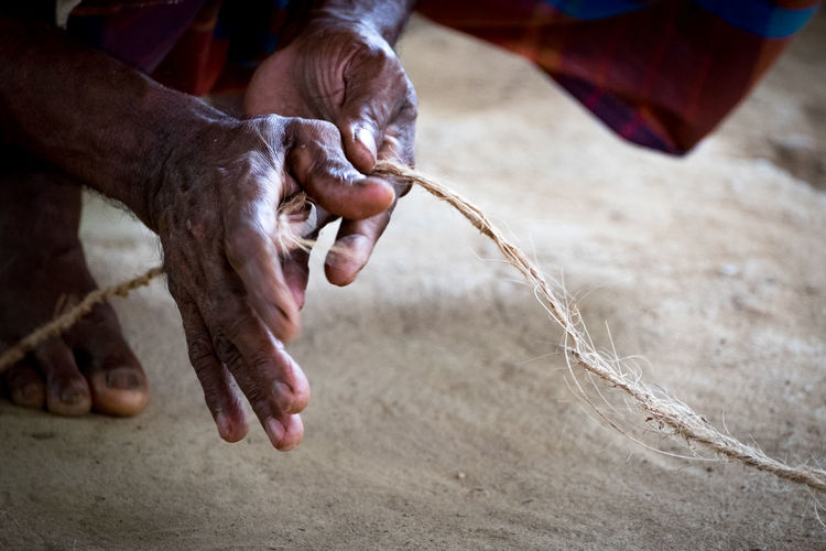 Hands weaving coconut rope