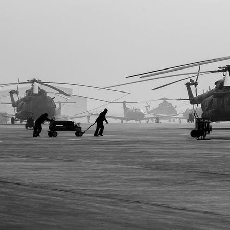 Afghan Air Force airmen pull a nitrogen cart to a Mi-17. At Kabul international airport. brightFuture photography nofilter b&w blackandwhite military photooftheday helicopter reportagespotlight DoD Defense followme