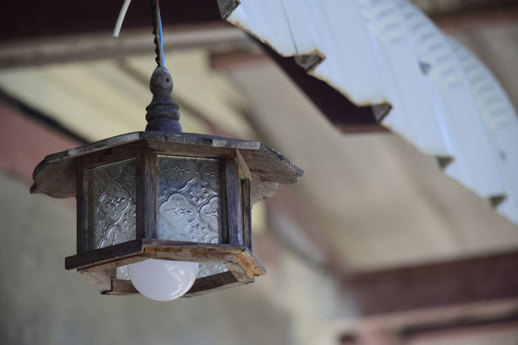 Low angle view of lantern hanging in old building