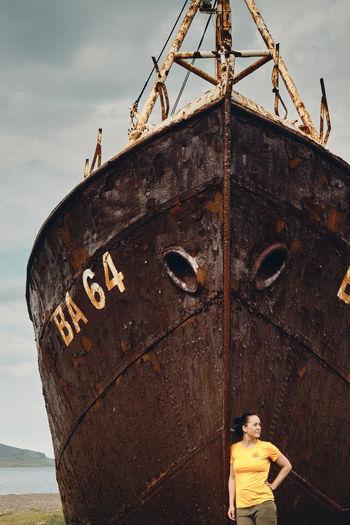 Portrait of man on rusty ship against sky