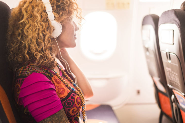 Side View Of Woman Listening Music While Sitting In Airplane
