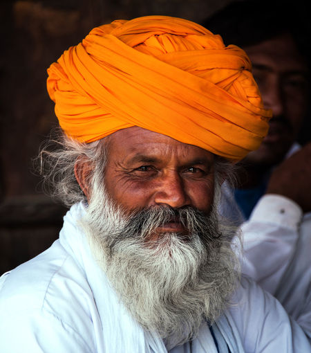 Indian gentleman looking at camera and proudly sporting a spectacular orange turban in the Indian state of Rajasthan India Traditional Clothing Adult Beard Clothing Contemplation Culture Front View Headshot Human Face Lifestyles Mature Adult Mature Men Men Mustache One Person Orange Color Portrait Rajasthan Real People Senior Adult Tourism Travel Portraits Turban White Beard