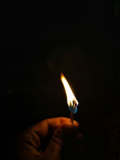 Close-up of hand holding burning matchstick over black background