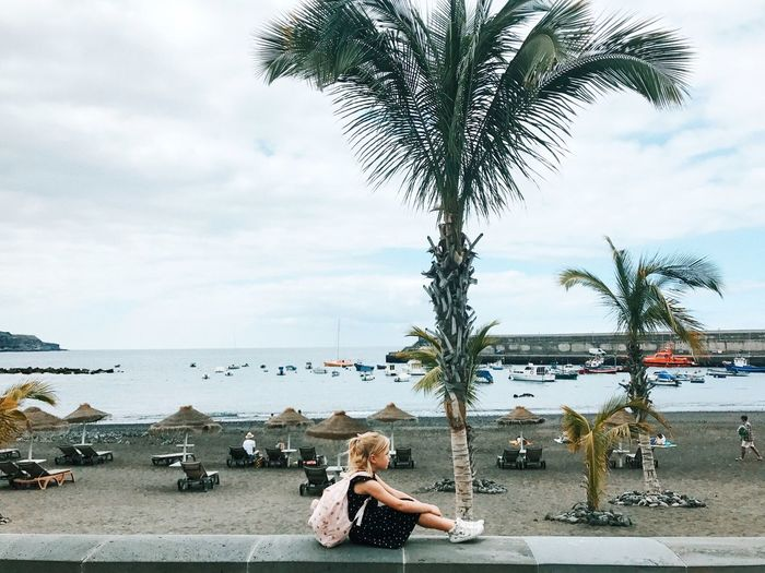 Little girl Water Real People Sky Tree One Person Beach Plant Nature Lifestyles Cloud - Sky Childhood Sea Child Palm Tree Day Land Sitting Outdoors Leisure Activity