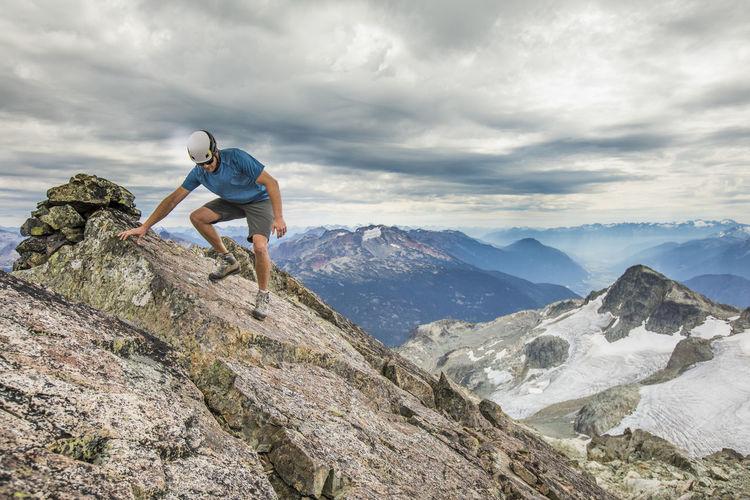 Man climbing rock on mountain against sky