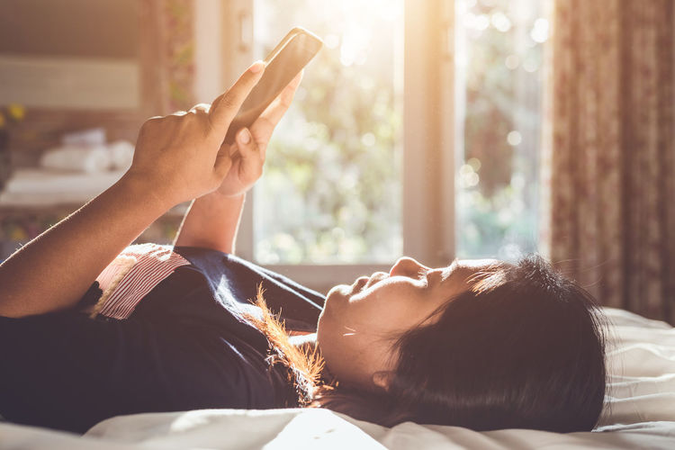 Midsection of woman using mobile phone while relaxing on bed