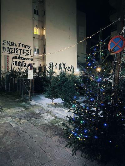 Illuminated christmas tree on street at night