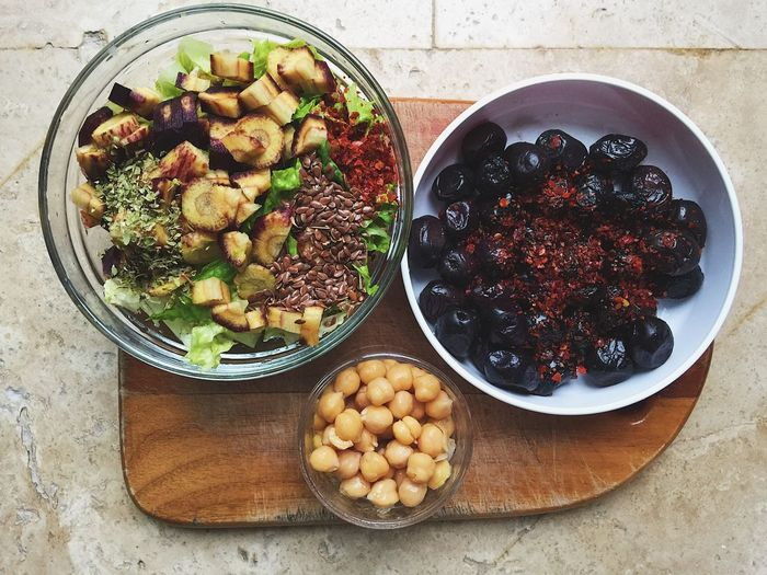 Directly above shot of salad with flax seeds and black olives in bowls on cutting board