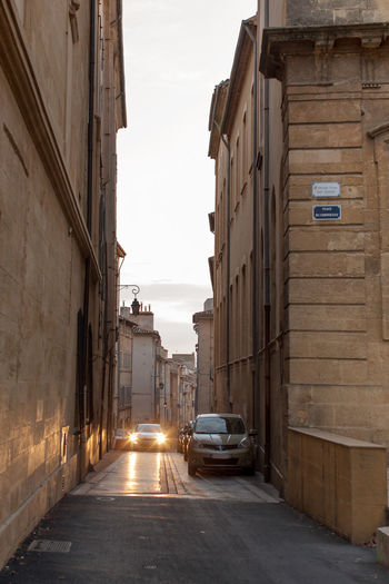 A street in the Old city of Aix-en-Provence Architecture Building Exterior Built Structure Car City City Life Day Diminishing Perspective Illuminated In Front Of Land Vehicle Mode Of Transport Outdoors Parked Sky Stationary Street Tail Light The Way Forward Transportation