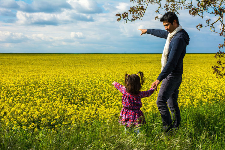 Father and daughter holding hands while standing on field against sky
