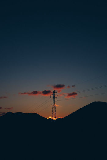 Low angle view silhouette of electricity pylon against sky during sunset
