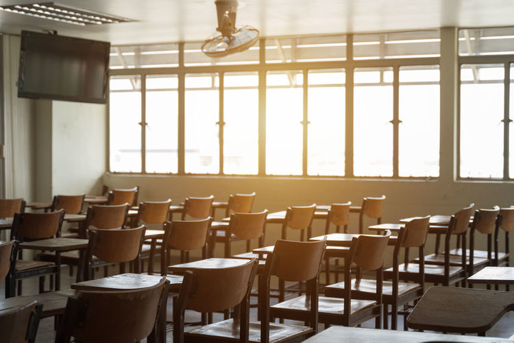 Classroom with a lot of wooden chairs. Absence Arrangement Business Cafe Ceiling Chair Day Education Electric Lamp Empty Furniture In A Row Indoors  No People Order Restaurant Seat Setting Sunlight Table Window Wood - Material
