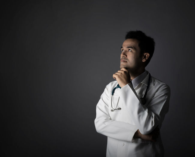 Thoughtful Doctor Over Black Background
