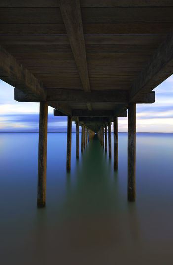 Low Angle View Of Pier On Sea Against Sky