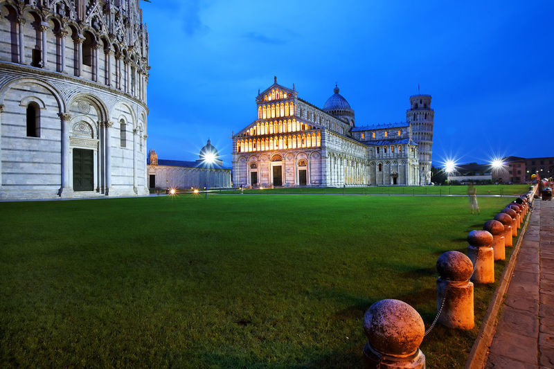 Pisa cathedral and leaning tower of pisa against blue sky at dusk