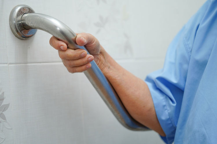Midsection of person holding handle in bathroom