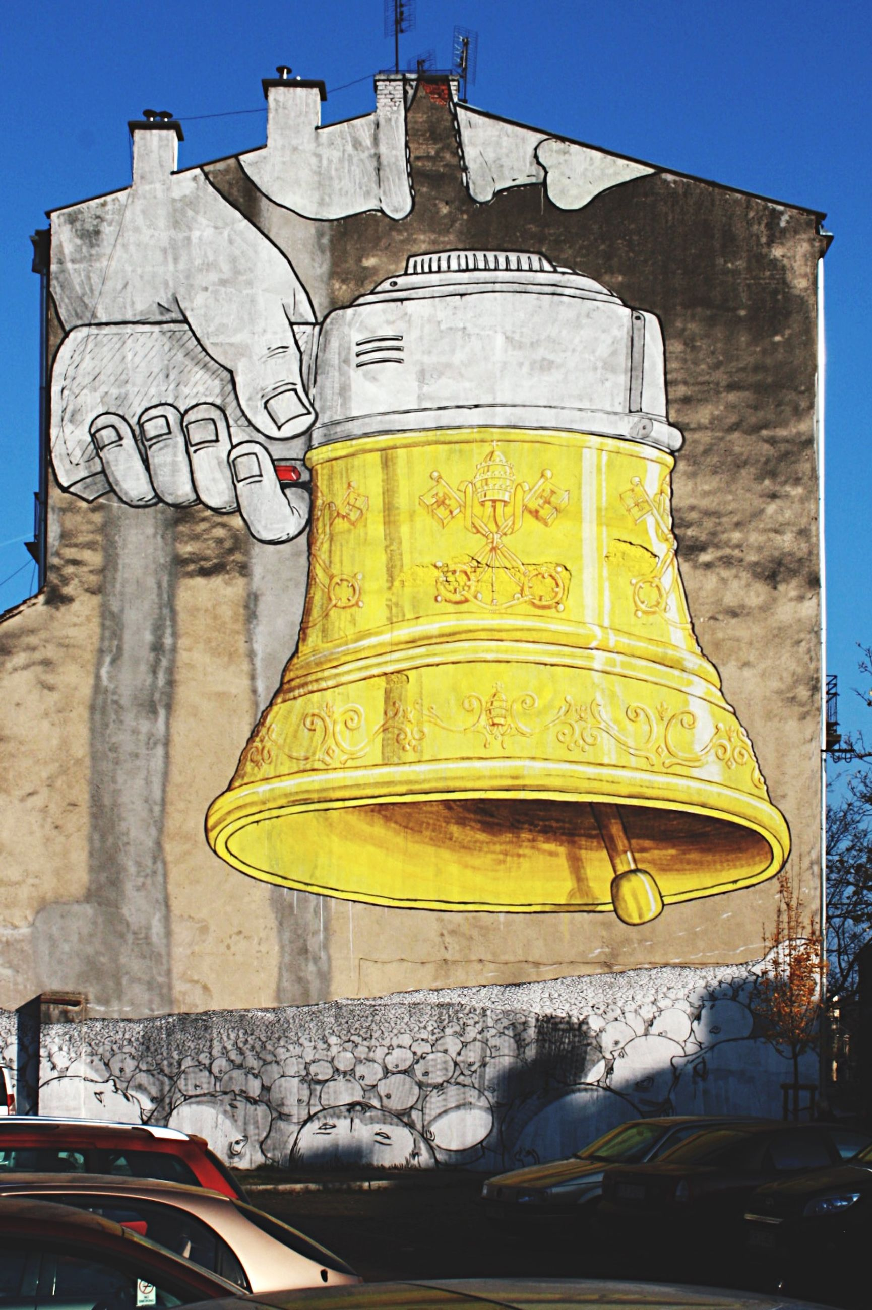 architecture, built structure, building exterior, low angle view, clear sky, text, blue, western script, art, communication, art and craft, yellow, graffiti, creativity, sunlight, human representation, day, outdoors, history, no people