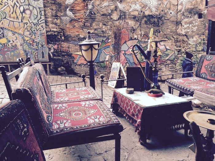 Hookah on table by empty chairs against graffiti on wall