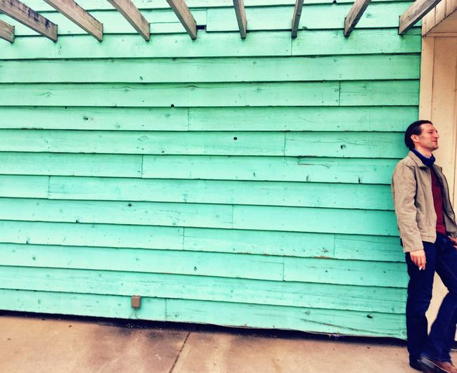 Man Leaning On Blue Wooden Wall
