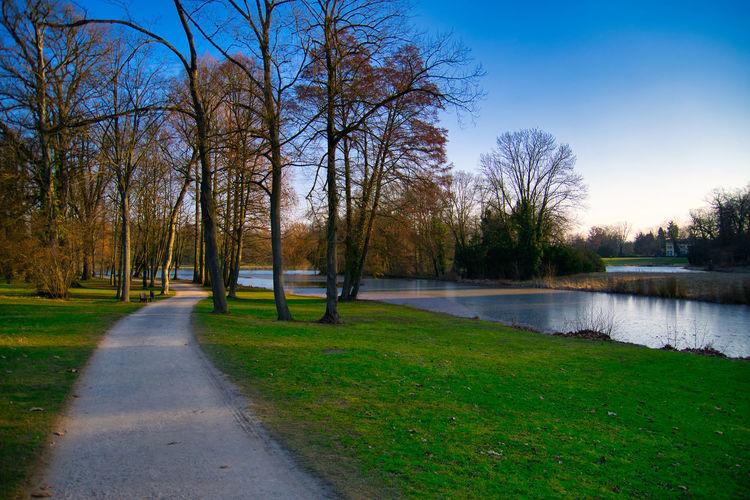 Footpath by lake in park against sky
