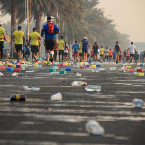 Bottles On Street Against People Running In Marathon