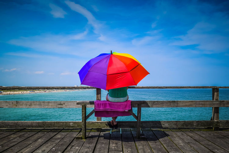 Person with umbrella sitting in front of sea