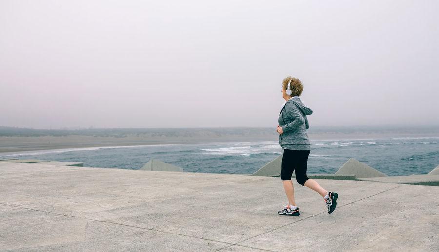 Woman jogging on pier against sky