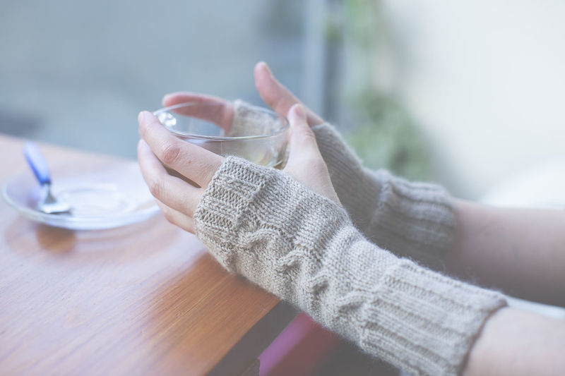 Cropped Image Of Woman Wearing Mitten Holding Tea Cup At Cafe