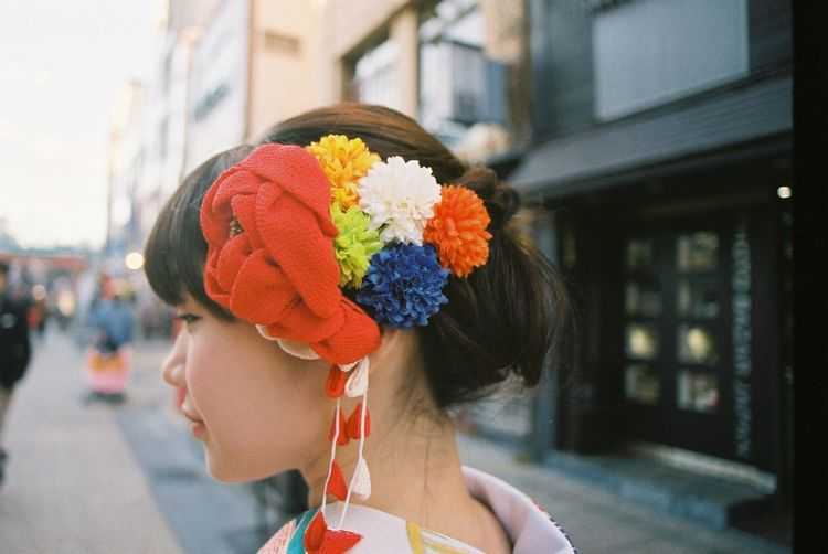 Side View Of Asian Woman Wearing Flowers While Standing Building In City