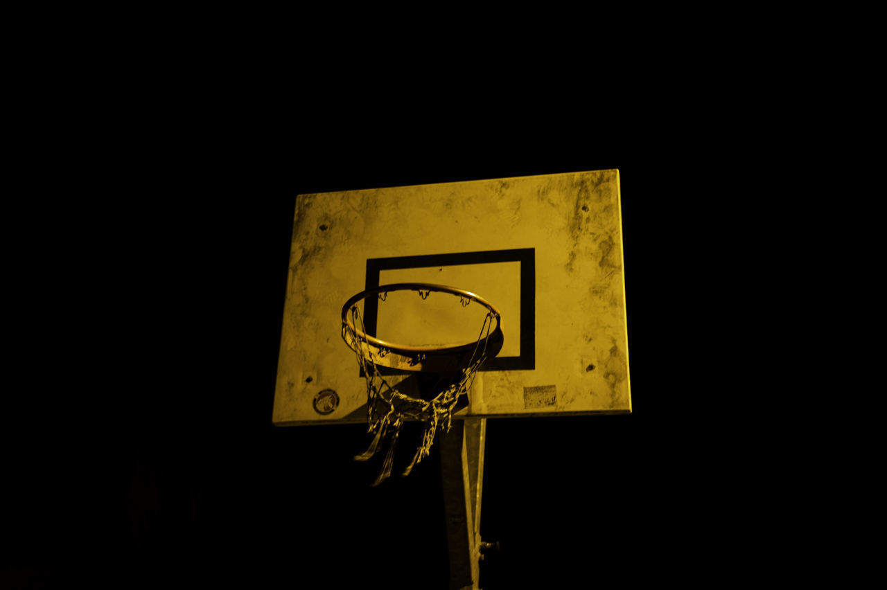 CLOSE-UP OF BASKETBALL HOOP AGAINST DARK BACKGROUND
