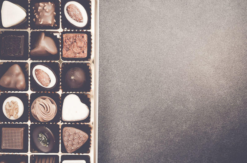 Directly above shot of various chocolates in box on table