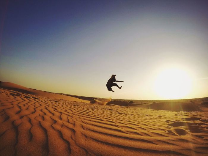 India, Rajasthan, Udaipur Mid-air Sand Real People Full Length Lifestyles One Person Nature Outdoors Jumping Men Sky Day Sand Dune Energetic Thar Desert Jaisalmer India Rajasthan Heat - Temperature Desert Scenics Extreme Terrain Sun Landscape Tranquil Scene