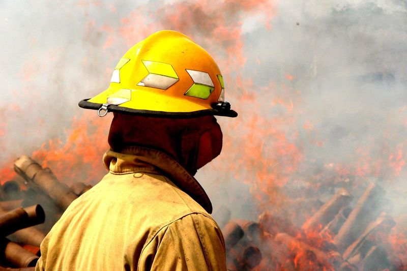 Side view of firefighter standing against fire