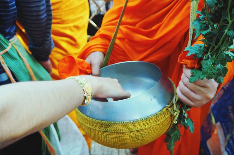 Cropped hand over container being held by monk