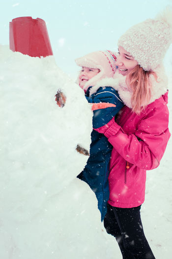 Girl and her little sister making a snowman, spending time together outdoors, having fun in wintertime Winter Wintertime Snowman Fun Snow Snowing Outdoors Lifestyles Cold Wintery Season  White Enjoying Life Enjoyment Leisure Happiness Child Childhood Girl Kid Family People Siblings Building Happy