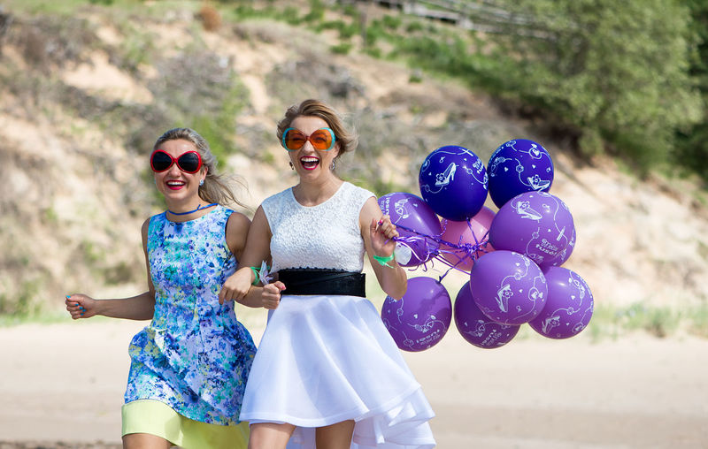 Women wearing sunglasses with balloons