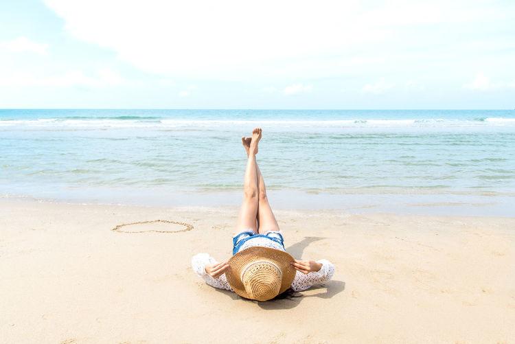 Woman lying on sand at beach against sky