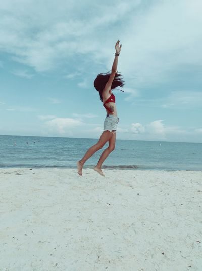 Side view of woman jumping at beach against blue sky