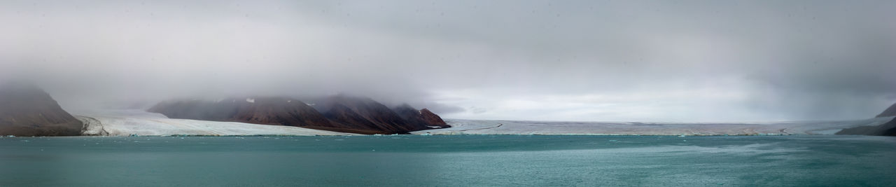 Scenic view of ellesmere glacier against sky during canadian arctic summer.