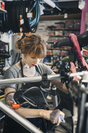 Woman looking through bicycle at store