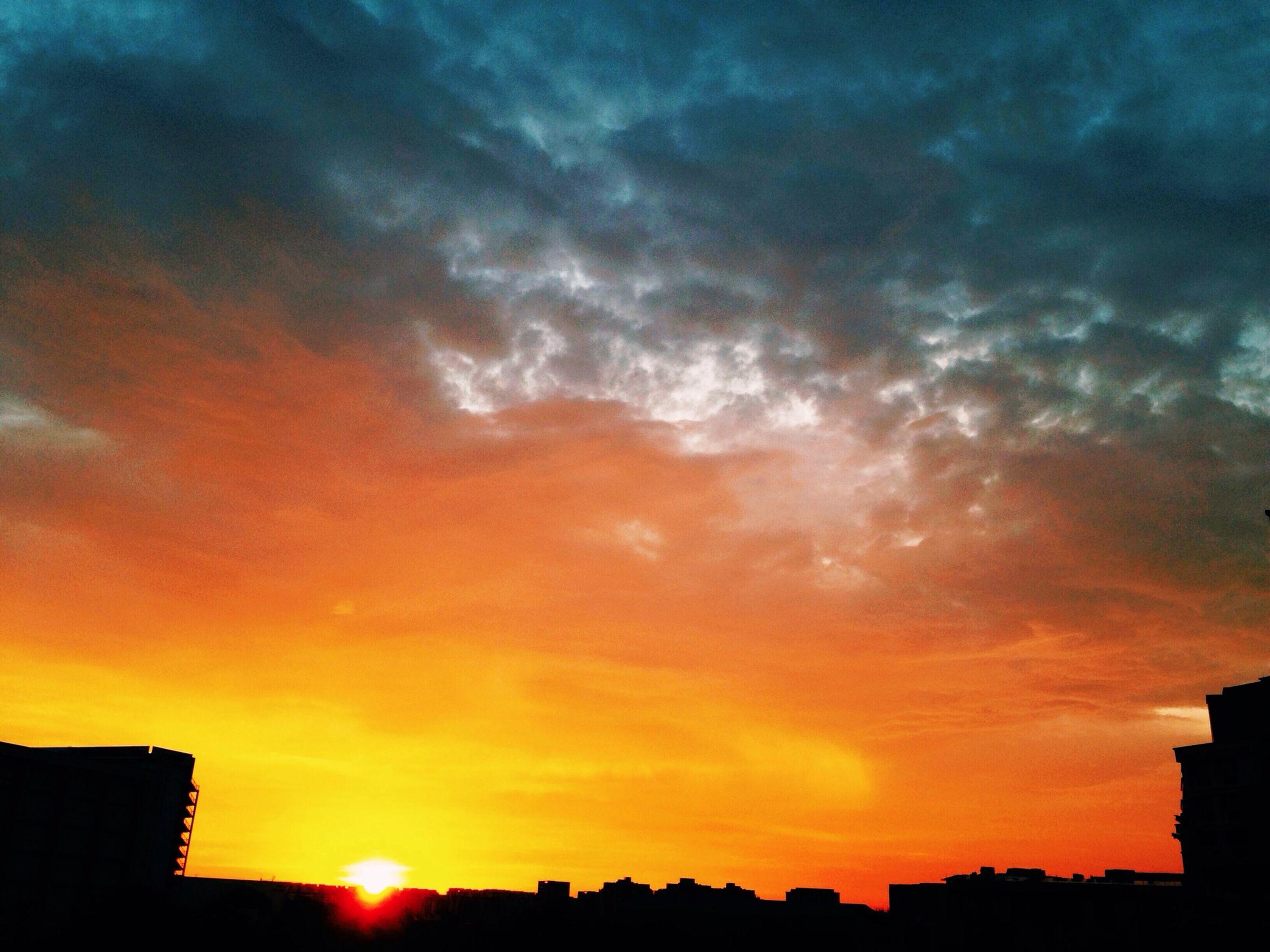 sunset, building exterior, architecture, built structure, silhouette, sky, orange color, cloud - sky, sun, low angle view, city, beauty in nature, sunlight, building, cloud, dramatic sky, cloudy, nature, residential building, scenics