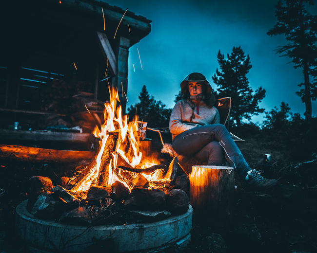 High angle view of woman sitting by bonfire