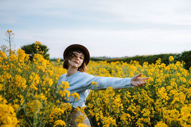 Portrait of woman standing amidst flowers