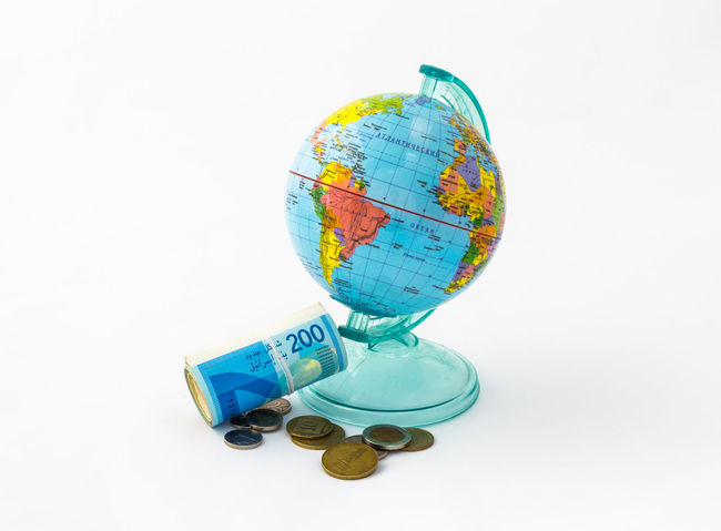 A money box made in the form of a globe, the planet Earth with a money slot at the top stands near a rolled up and held together stack of Israeli banknotes of different value with several coins, isolated on a white background. Business Currency Earning Earth Isolated Art Bank Banknote Buy Cash Coin Coins Design Exchange Finance Globe Israel Money Pay Planet Shekel Stock Studio Shot Wealth White Background