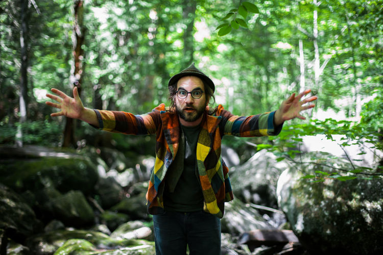 Young man with arms outstretched standing in forest