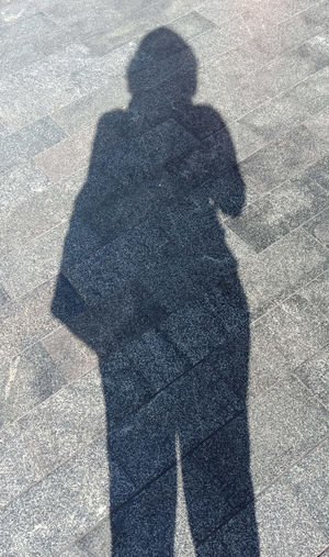 Low section of man shadow on floor
