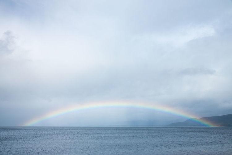 Rainbow over sea against cloudy sky