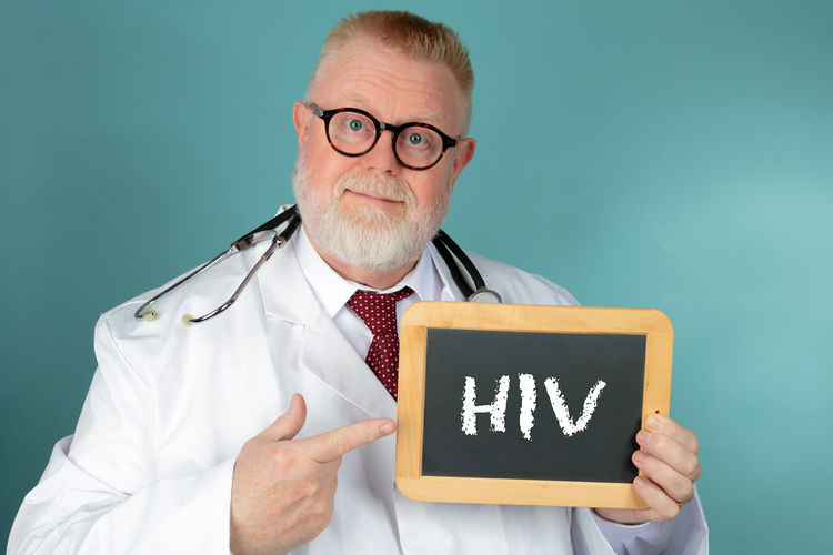 Portrait of male doctor holding slate with hiv text against green background
